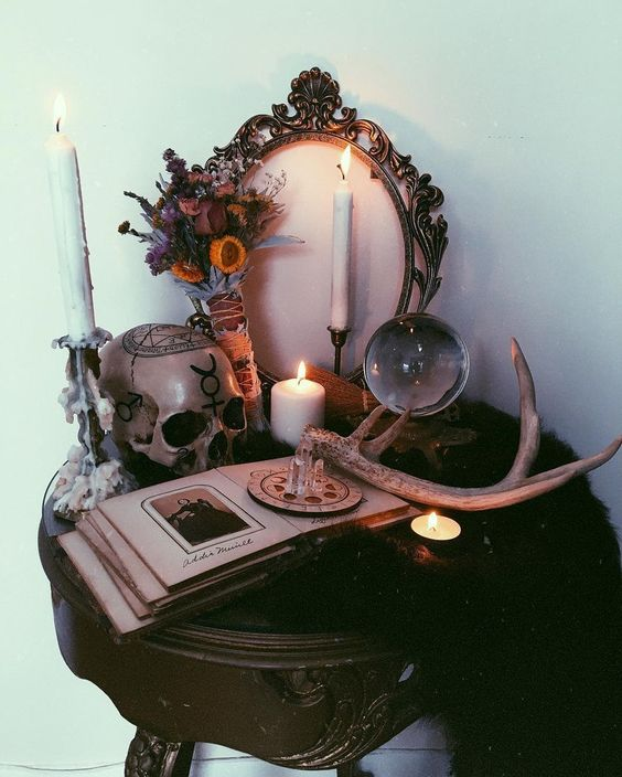 a boho Halloween table with dried blooms, antlers, candles, a vintage photo album and a painted skull