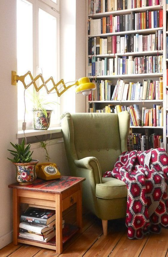 a retro cozy reading nook with a large bookcase, a green wingback chair and a yellow wall lamp is very comfortable