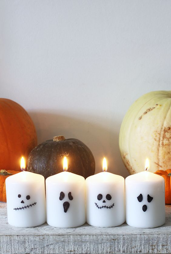 decorate simple white candles with a black sharpie making some scary faces and voila - you have Halloween candles