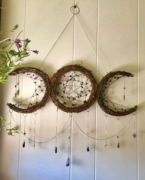 a boho-like Halloween decoration of vine showing lunar spheres, weaving, crystals and stars is amazing