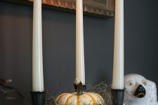 14 a bowl with hay, a pumpkin and three candleholders in black is a stylish and scary idea for Halloween