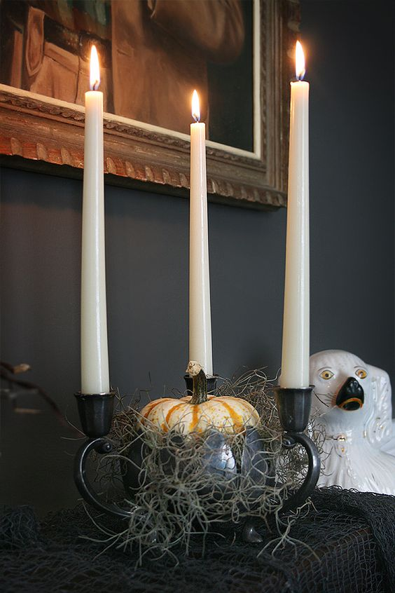a bowl with hay, a pumpkin and three candleholders in black is a stylish and scary idea for Halloween