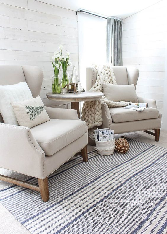 a seaside cottage space done with neutral wingback chairs and pillows and chunky knit blanket