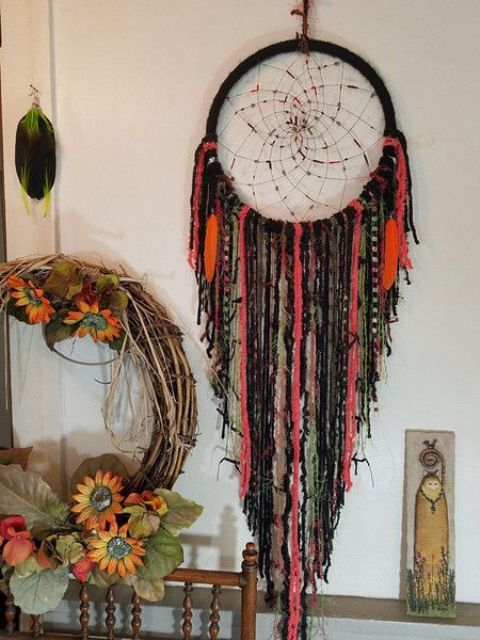 a gothic boho dreamcatcher in bright colors and black, with beads and fabric is great for Halloween decor