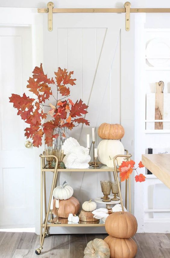 a modern elegant bar cart with stacked pumpkins, bright leaves in vases, candles and stained glasses is very chic