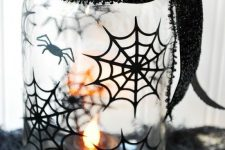 16 a sheer mason jar decorated with blakc spiderwebs and spiders plus a black glitter ribbon will be a nice candleholder