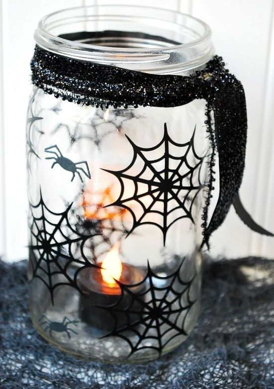 a sheer mason jar decorated with blakc spiderwebs and spiders plus a black glitter ribbon will be a nice candleholder