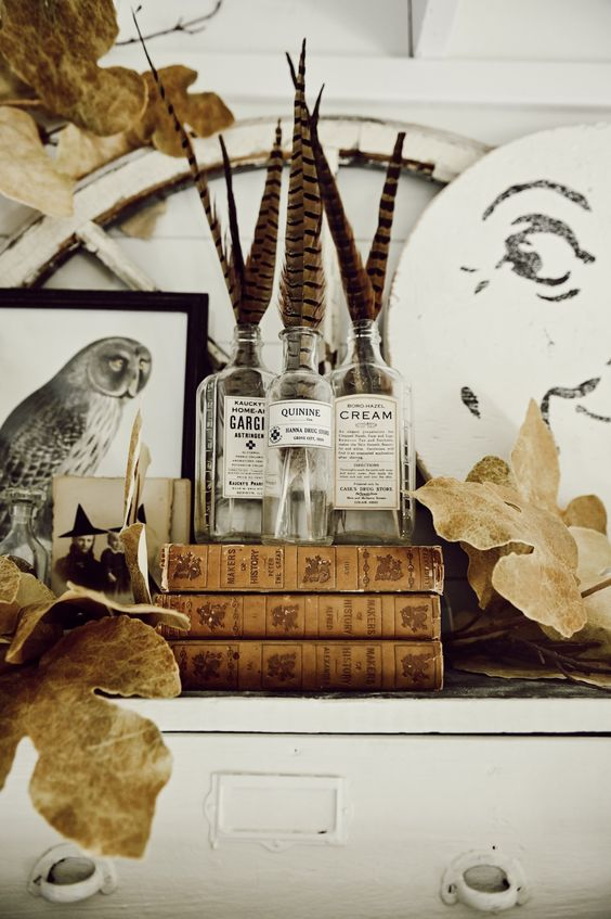a vintage boho Halloween mantel with feathers in bottles, an owl artwork, dried leaves and a lunar artwork