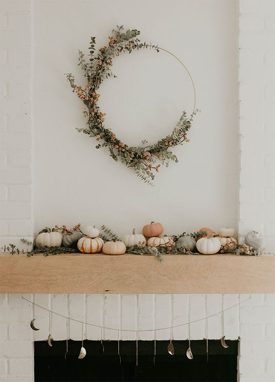 a stylish and natural fall mantel with natural pumpkins, greenery, berries and a matching round wreath over the mantel
