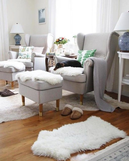 dove grey wingback chairs by IKEA with matching footrests, faux fur and pillows form a very cozy nook