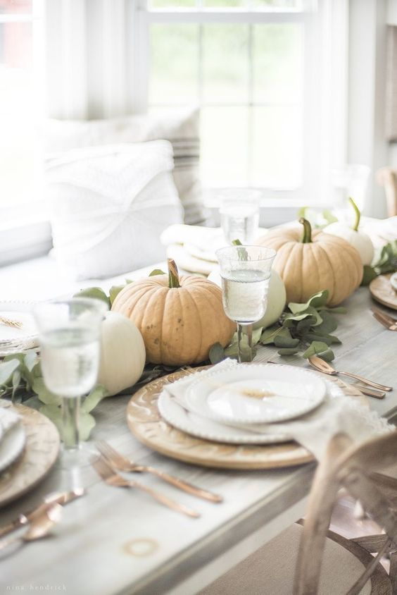 a neutral and chic fall tablescape with greenery and natural pumpkins, patterned plates and copper cutlery is easy to recreate