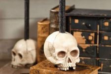 18 a skull candleholder with a black candle is a stylish Halloween decor idea to rock and it looks bold