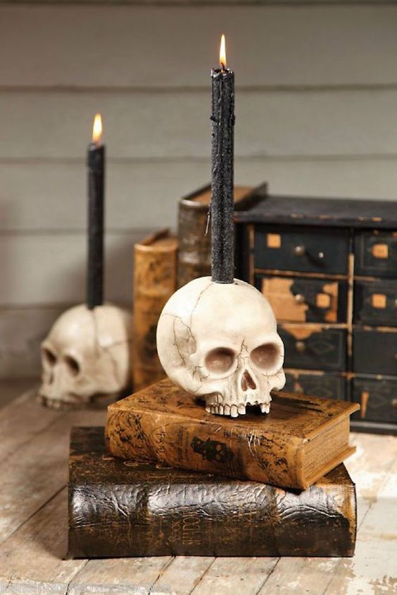 a skull candleholder with a black candle is a stylish Halloween decor idea to rock and it looks bold