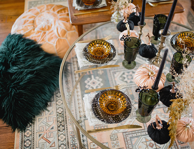 boho Halloween party styling with printed plates, black and peachy pumpkins, green glasses and some branches