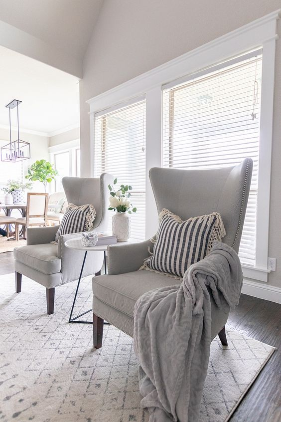 dove grey wingback chairs with decorative nails, blankets and pillows for a cozy nook in your space
