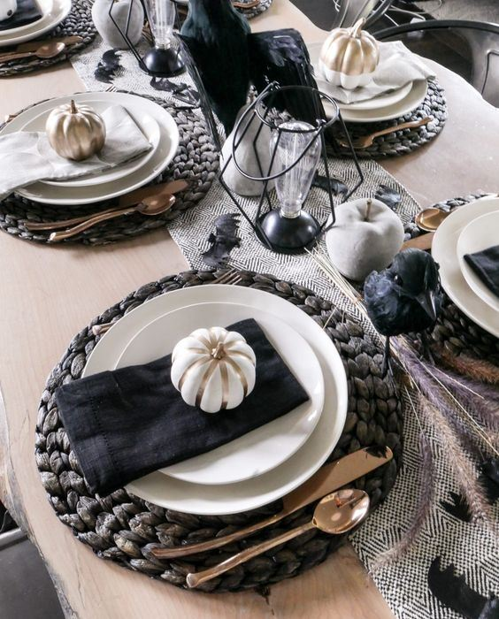 a gorgeous fall tablescape with a printed runner, white and gilded apples and pumpkins, black napkins and metallic cutlery