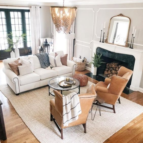an eclectic living room done in neutrals, with brown leather wingback chairs and a matching ottoman, a boho chandelier and a fireplace