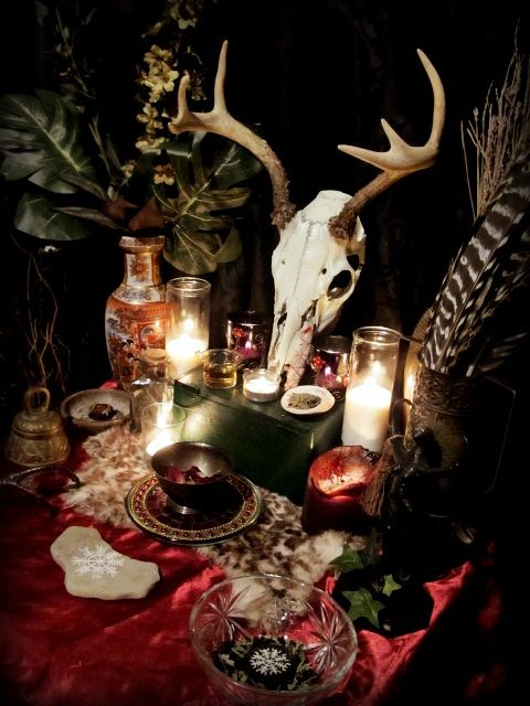 boho witch Halloween styling with green leaves, an animal skull, feathers, crystals, candles and faux fur