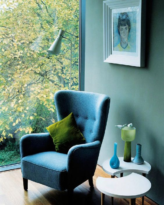 a beautiful blue nook with a blue wingback chair by the winfow, a bold artwork and accessories for decorating