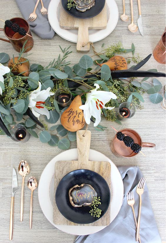 a modern fall tablescape with copper cutlery, eucalyptus, antlers, white blooms, pears and copper mugs