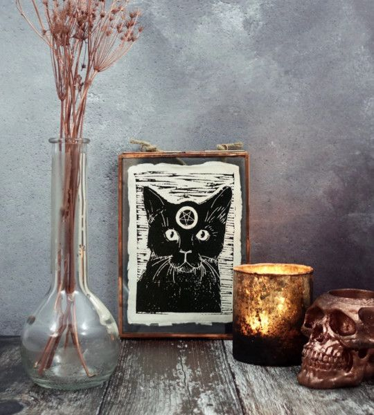 dried blooms in a vase, a candle, a copper skull and a witch's familiar art for a cool boho Halloween party