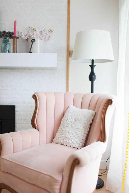 a cozy girlish reading nook with an exquisite blush wingback chair, a petal pillow and a table lamp