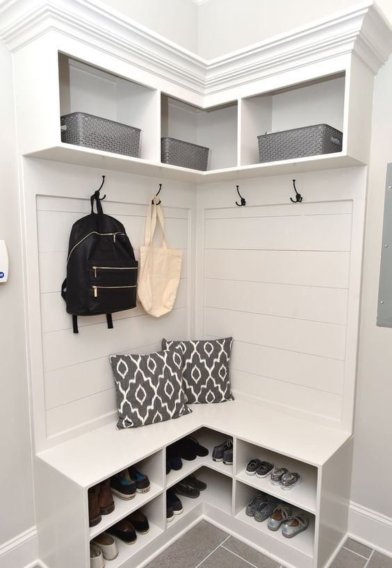 a mudroom organized with a white wooden storage unit with open shelves and hooks is a stylish idea to rock