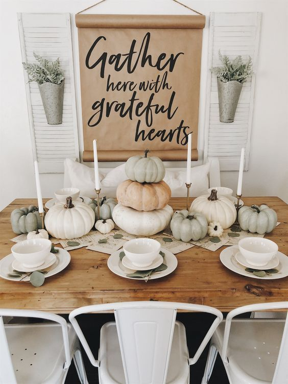 a neutral modern fall tablescape with stacked pumpkins, leaves, white candles and simple dishes