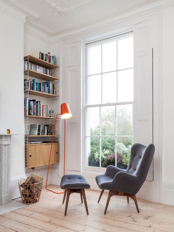 a mid-century modern reading nook with a suspended bookshelf, a grey and orange wingback chair plus a footrest