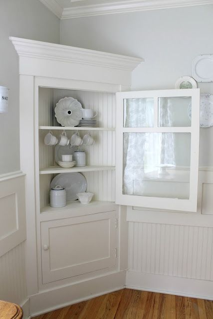 a neutral corner vintage storage unit with a glass door is a comfy and stylish piece to rock