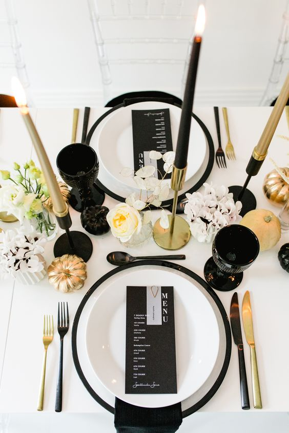 a refined modern fall tablescape with black plates, glasses, gold and black candles and cutlery plus blooms and pumpkins