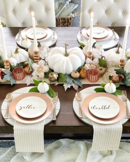 a refined neutral Thanksgiving tablescape with neutral linens, white candles, leaves, white and metallic pumpkins and gourds