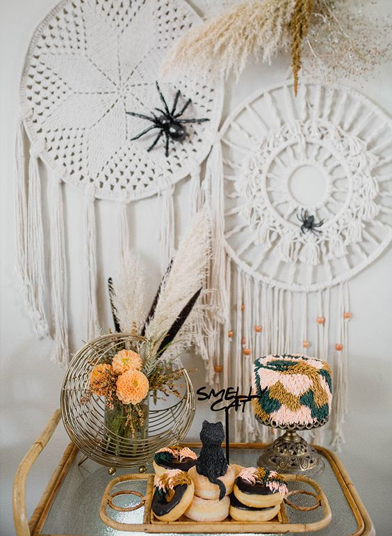 macrame hangings with spiders and beads, feathers and pampas grass and donuts topped with a chocolate cat