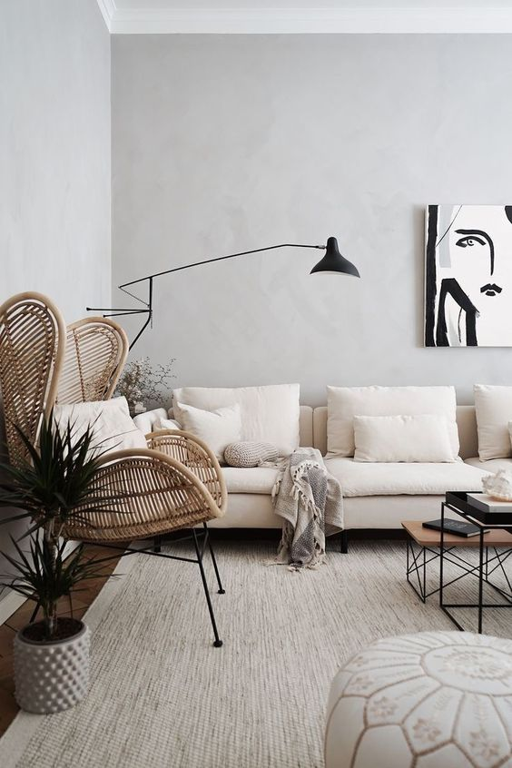 a stylish Scandinavian living room done in neutrals with a rattan wingback chair and black touches for more drama