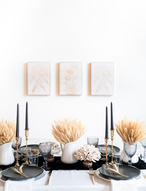 a stylish modern fall tablescape with black plates, candles and a table runner, gold cutlery and candleholders and wheat bundles