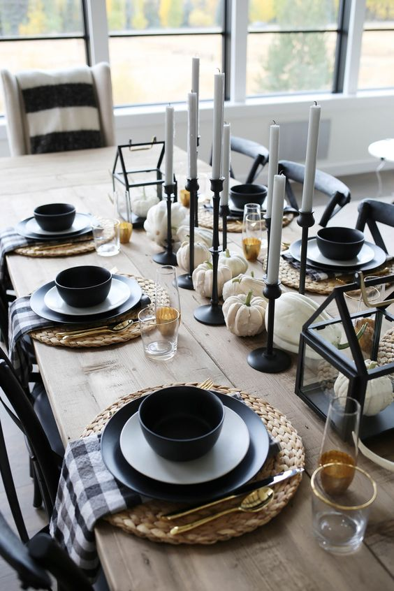 a stylish modern farmhouse tablescape with woven mats, black plates and candleholders, plaid napkins, white pumpkins