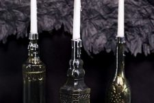 25 vintage bottles painted black and bronze to make the look like refined metal candleholders are chic and elegant
