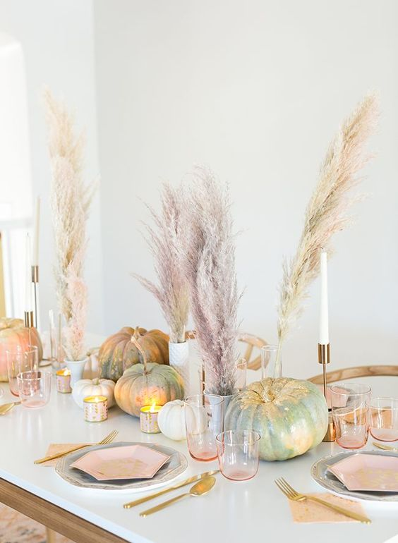 a stylish modern pastel fall table setting with blush menus and glasses, gold cutlery and candleholders plus pastel pampas grass