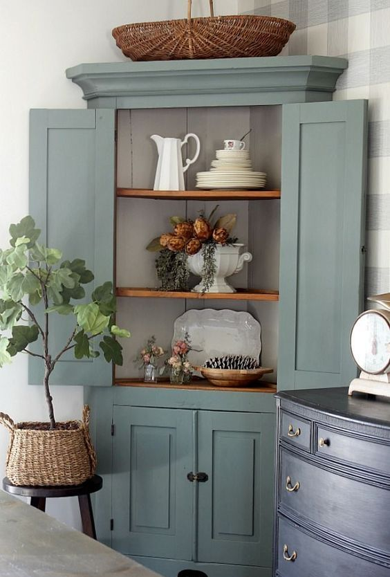 a vintage corner cabinet painted green, with rustic shelves is a stylish refined piece to store your things