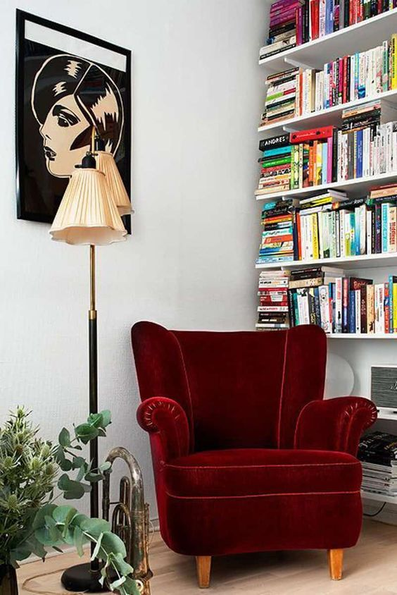a whimsical reading nook with a burgundy velvet wingback chair, a bookshelf, a bold artwork and greenery