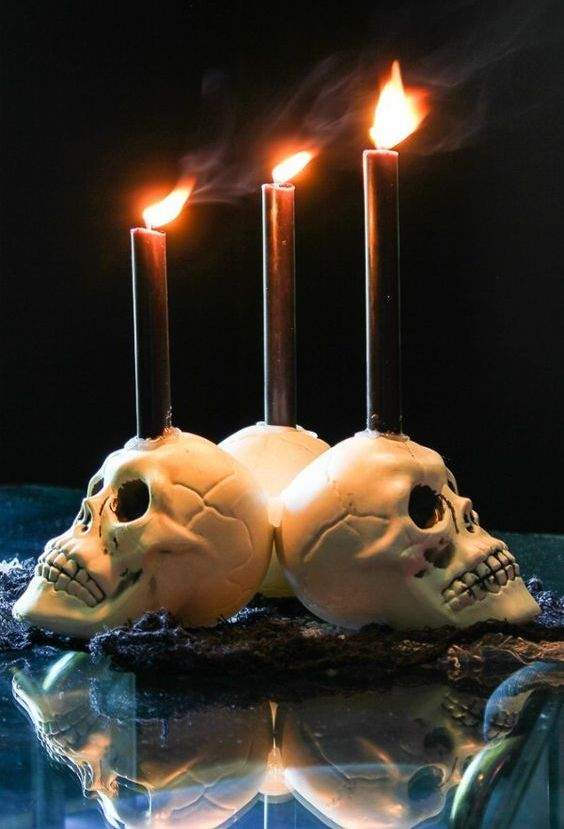 white skull candleholders with black candles are perfect for decorating your space for Halloween, simple and traditional