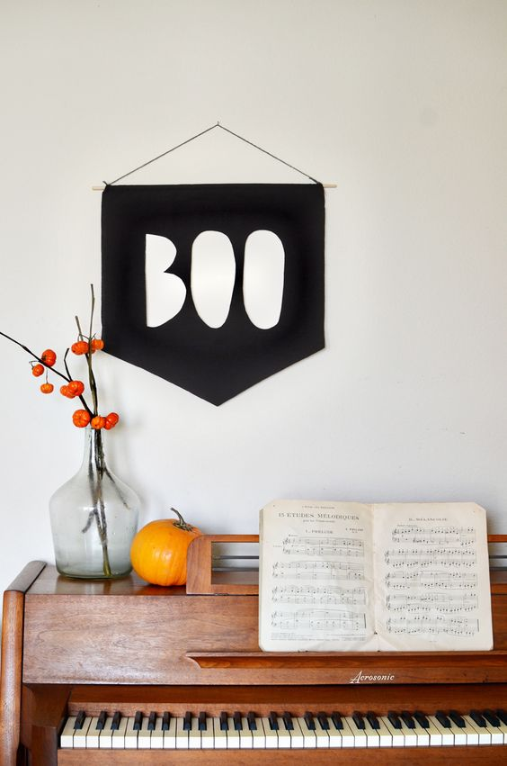 a BOO banner, a pumpkins and dried blooms in a bottle for simple and minimal Halloween styling