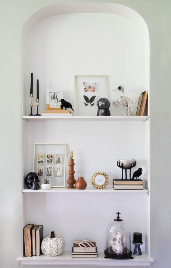 a Halloween bookshelf styled with black candles, skeletons, taxidermy, pumpkins and a skull in a cloche