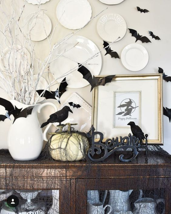 a Halloween console with a pumpkin, letters, blackbirds, and plates on the wall is very contrasting and bold