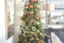 a Thanksgiving tree with faux and velvet pumpkins, pinecones, foliage, greenery and branches with berries plus more pumpkins under it
