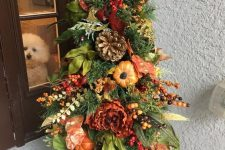 a Thanksgiving tree with faux blooms, pumpkins, fruits, berries, greenery and oversized pinecones is very lush