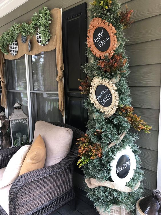 a Thanksgiving tree with faux leaves and chalkboard signs in vintage frames is a stylish piece for indoors or outdoors