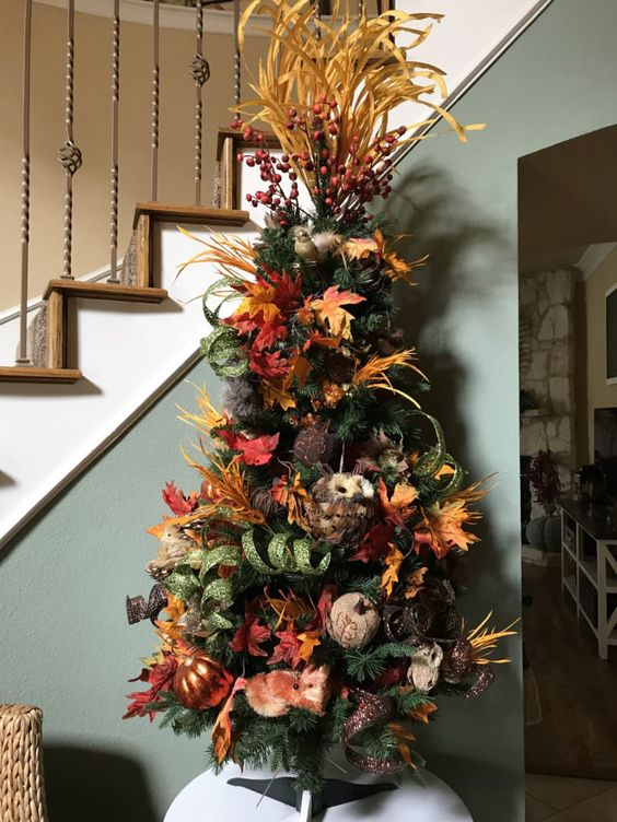 a Thanksgiving tree with leaves, faux and fabric pumpkins, faux leaves, husks, berries and glitter ribbons