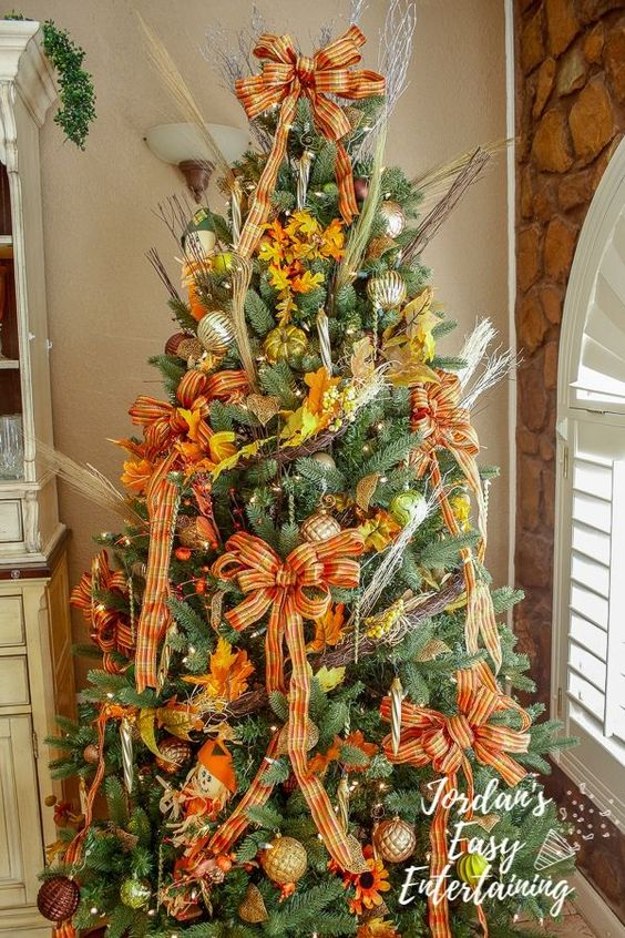 a Thanksgiving tree with lights, plaid ribbon bows, gilded pumpkins, fall leaves, twigs and shiny metallic ornaments