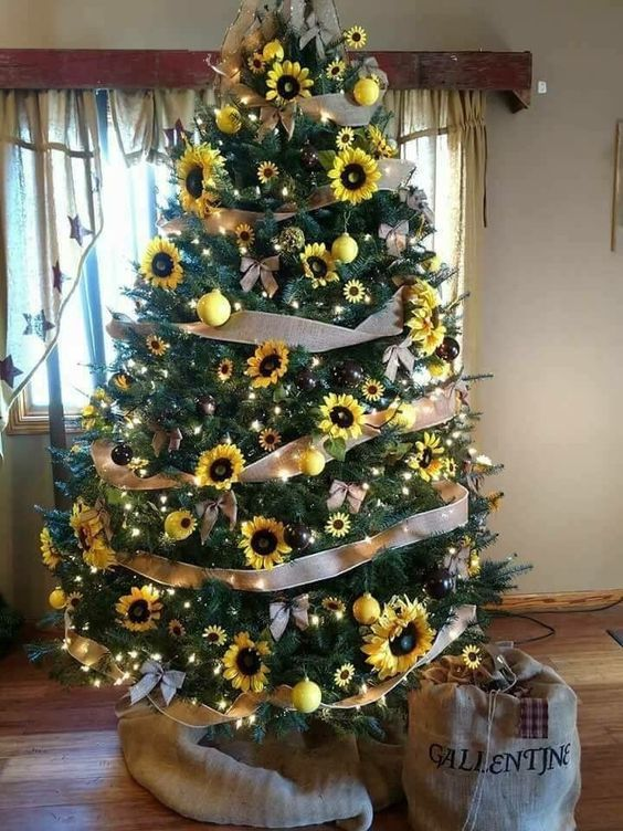 a Thanksgiving tree with ribbons, sunflowers and faux yellow blooms, yellow and black ornaments and lights